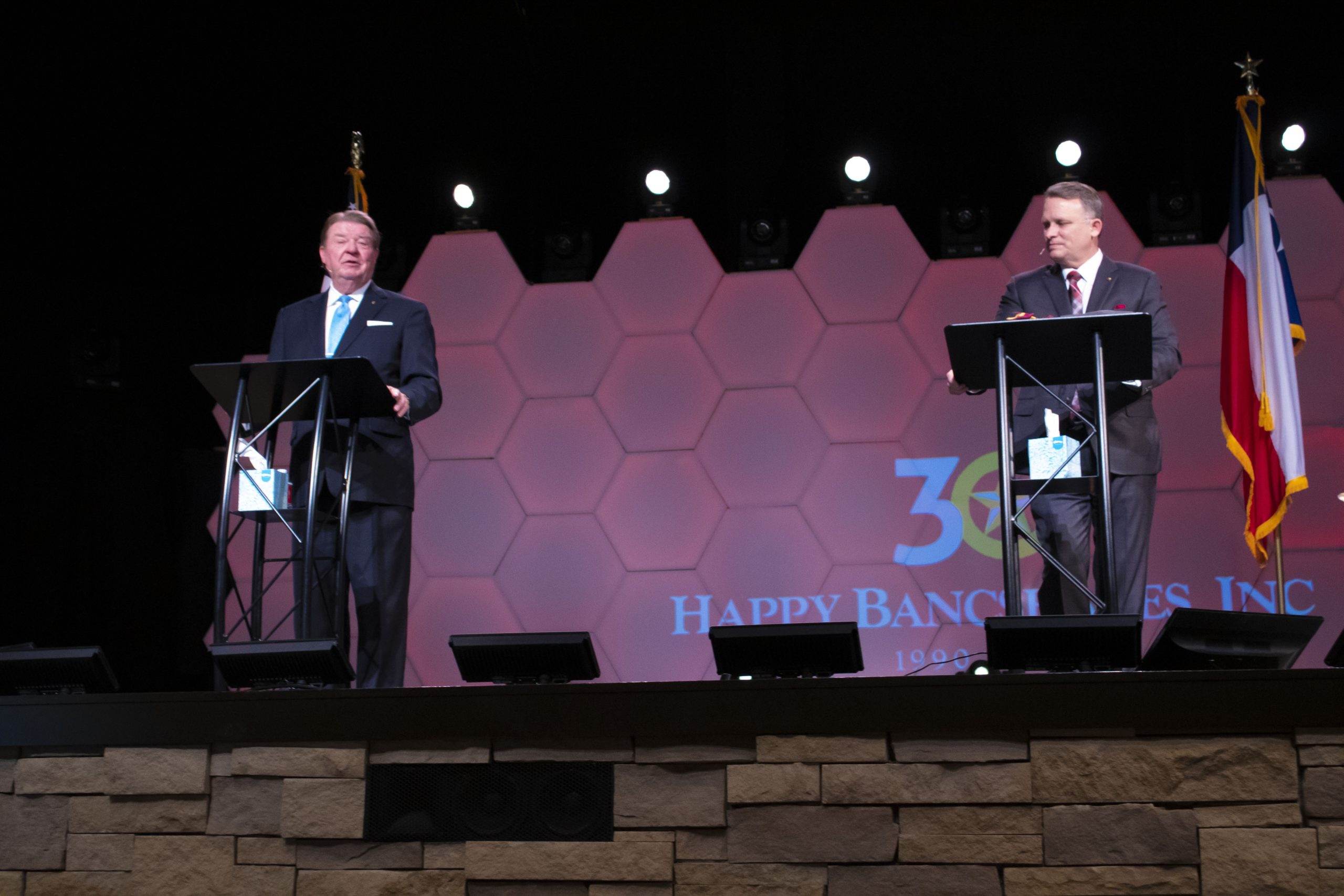 Two men stand on a stage.