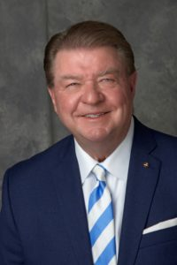 Headshot of smiling older man in a suit.