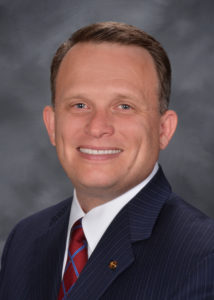 Headshot of a smiling man in a suit.